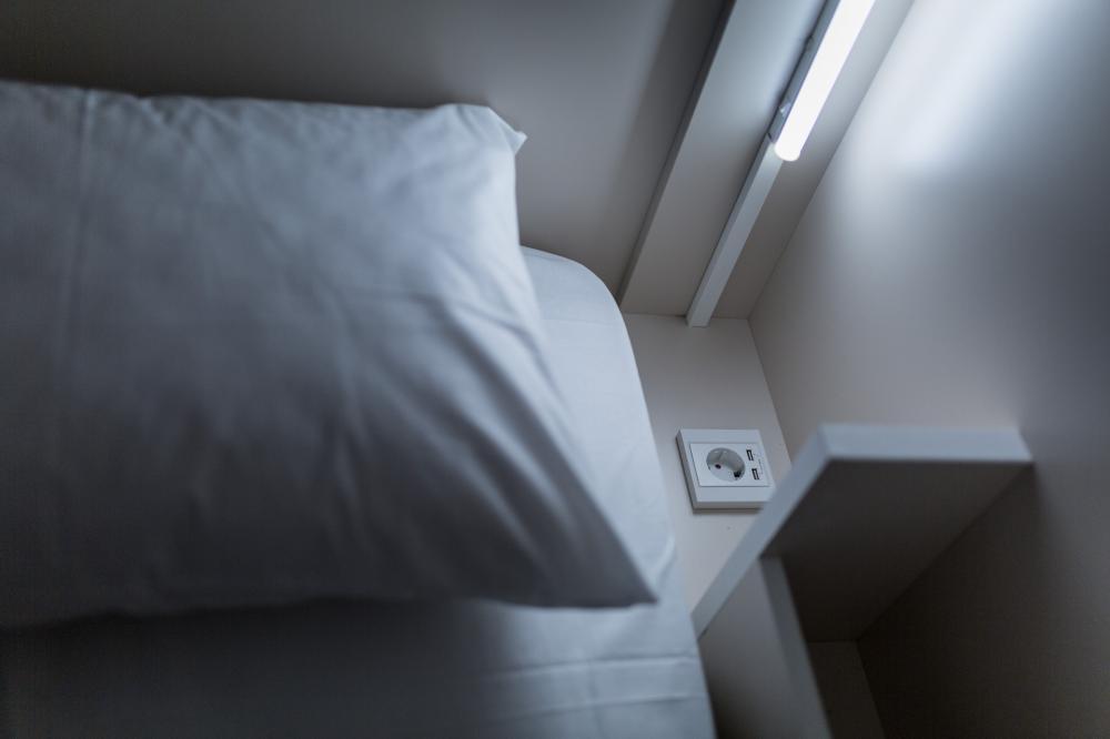 Steckdose und Leselampe neben dem Bett